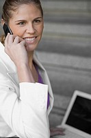 Side profile of a businesswoman talking on a mobile phone and smiling