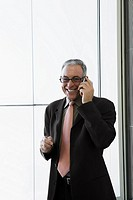 Businessman talking on a mobile phone and smiling in the waiting room of an airport