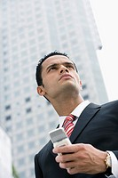 Low angle view of a businessman holding a mobile phone