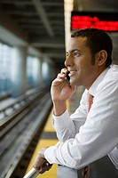 Side profile of a businessman talking on a mobile phone at a subway station