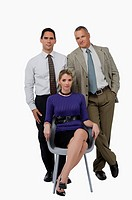 Portrait of a businesswoman sitting on a chair with two businessmen standing behind her