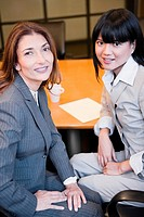 Portrait of two businesswomen sitting in a board room