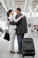 Businessman and a businesswoman standing at an airport with their arms around each other