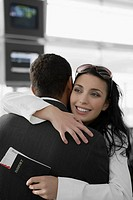 Close_up of a businesswoman hugging a businessman at an airport