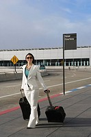 Businesswoman pulling her luggage outside an airport