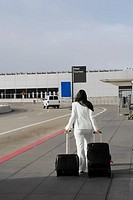 Rear view of a businesswoman pulling her luggage outside an airport
