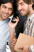 Close_up of two male university students listening to a mobile phone