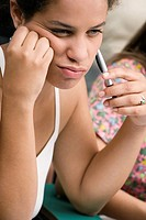 Close_up of a teenage girl holding a pen and thinking