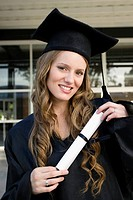 Portrait of a female graduate holding her degree and smiling