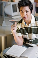 Portrait of a young man sitting in a computer lab and smiling