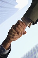 Low angle view of two people shaking hands