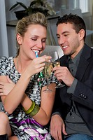 Young couple toasting with champagne flutes and smiling