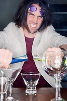 Portrait of a young man making a cocktail