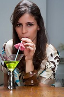 Portrait of a young woman drinking cocktail