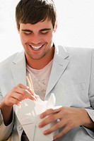 Close_up of a young man holding chopsticks and smiling