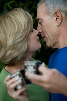 Close_up of a senior man and a mature woman holding tea cups and kissing each other
