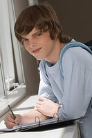 Portrait of a teenage boy writing on spiral notebook and smiling