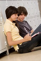 Side profile of a teenage boy and a teenage girl reading a book