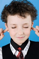 Close_up of a boy with his fingers in his ears