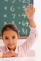 Portrait of a schoolgirl with her hand raised in a classroom (thumbnail)