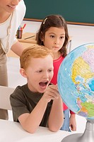 Schoolboy looking at a globe and shouting with a schoolgirl and a female teacher standing behind him