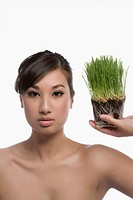 Portrait of a young woman holding wheatgrass (thumbnail)