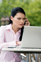 Close-up of a businesswoman talking on a mobile phone while using a laptop (thumbnail)