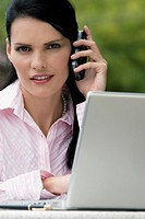 Portrait of a businesswoman talking on a mobile phone while using a laptop