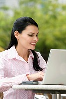 Close_up of a businesswoman using a laptop and smiling