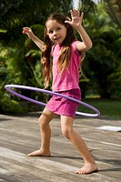 Side profile of a girl playing with a plastic hoop