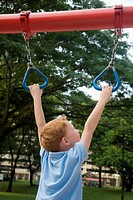 Rear view of a boy hanging on monkey bars