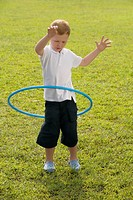 Boy playing with a plastic hoop in a park