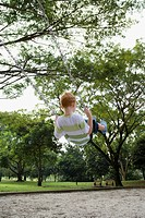 Rear view of a boy sitting on a chain swing ride in a park