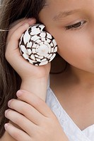 Close_up of a girl holding a spiral seashell close to her ear