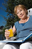 Low angle view of a senior woman sitting on a chair and drinking juice