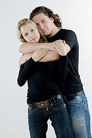 Portrait of a young man embracing a young woman from behind