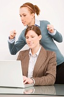 Businesswoman working on a laptop with her colleague clenching teeth behind her