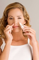 Portrait of a young woman putting nasal spray drops in her nose