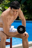 Close_up of a young man exercising with dumbbell