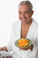 Portrait of a senior man holding a plate of orange and smiling
