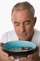 Close_up of a senior man holding a bowl with his eyes closed