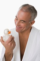 Close_up of a senior man holding a toy duck and smiling