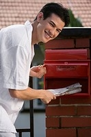 Portrait of a young man checking his mailbox and smiling