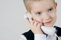 Close_up of a boy talking on the telephone