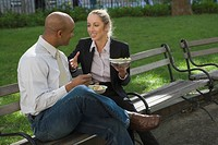 Businessman and a businesswoman having food on a park bench