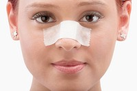 Close_up of a female patient with an adhesive bandage on her nose
