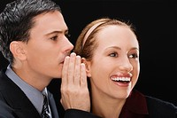 Side profile of a businessman whispering to a businesswoman
