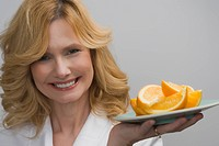 Portrait of a mature woman holding a plate of oranges and smiling