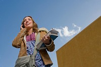 Low angle view of a young woman holding books and talking on a mobile phone