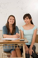 Portrait of a teenage girl and a female teacher sitting in a classroom and smiling